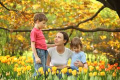 Mother With Children In Garden Among Tulips Stock Images