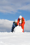 Mother With Kid Making Snowman Stock Photo