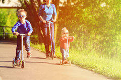 Mother With Kids Riding Scooters In Summer Stock Photos