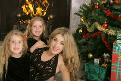 Mother With Twin Daughters By Fireplace Stock Images