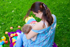 Mother woman breastfeeding baby boy kid. Mother women breastfeeding baby boy kid on background of grass in park Stock Photo