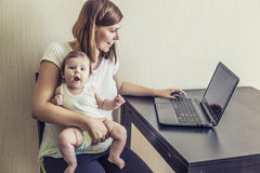 The mother of the woman with the child on hands at work behind t Stock Photo