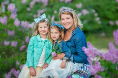 Mother woman with two cute smiling girls sisters lovely together on a lilac field bush all wearing stylish dresses and Stock Photo