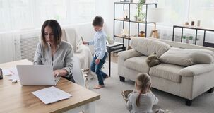 Mother working from home while children playing with toys