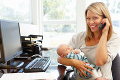 Mother working in home office with baby Royalty Free Stock Photos