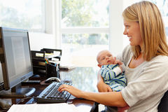 Mother working in home office with baby Royalty Free Stock Photography