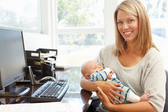 Mother working in home office with baby Stock Images