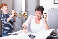 Mother is working in home office, son is disturbing by playing t. He trumpet Royalty Free Stock Photo