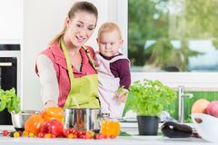 Mother working in kitchen while carrying child Stock Images