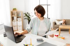 Mother working at laptop and baby boy at home royalty free stock photo