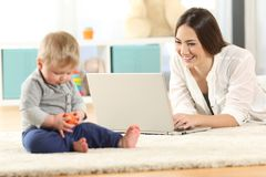 Mother working with a laptop and baby playing. With toys on the floor at home Royalty Free Stock Photo