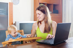 Mother working with laptop and baby Stock Photo