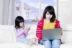 Mother working with laptop and her kid Royalty Free Stock Photography