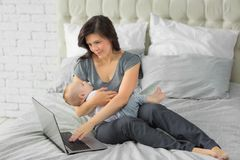 Mother working on laptop with a small child.  stock photos