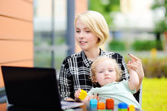 Mother working oh laptop and holding her toddler daughter Stock Photo
