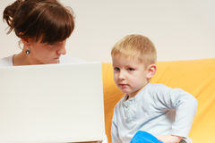 Mother working using laptop, little boy disturbing. Working at home problems concept. Mother working and using laptop her little boy disturbing Stock Photos