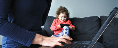 Mother works on laptop while her child plays on smartphone Royalty Free Stock Images