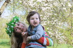 Mother in wreath and baby girl playing Royalty Free Stock Image