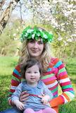 Mother in wreath and baby girl under spring trees Stock Photos