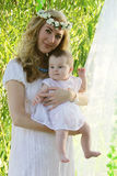 Mother with wreath holding baby girl Royalty Free Stock Photos