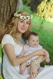 Mother in wreath holding baby girl Royalty Free Stock Image