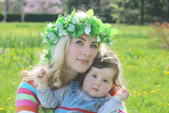 Mother in wreath hugging baby girl in spring lawn Stock Photos