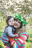 Mother in wreath hugging baby girl Royalty Free Stock Image