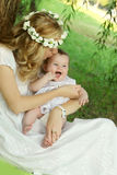 Mother in wreath kissing baby girl Stock Photography
