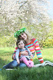 Mother in wreath sitting with baby girl under spring tree Royalty Free Stock Images