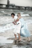 Mother wrestling teenager. Young mother in dress wrestling male teenager into sea Stock Images