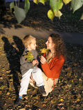 Mother wuth son. With autumn leaves on sunset light royalty free stock photo