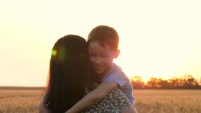Mother's Day. kids and mom silhouette. A mother holds her son in her arms. A cute child looks and smiles. A happy mother