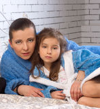 Mother and daughter are in the same blue robes. Mother and 5 year old daughter are in the same blue robes on the bed Royalty Free Stock Photos