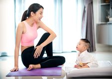 Mother in yoga action and baby in home stock images