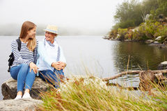 Mother and young adult daughter relaxing by a lake Royalty Free Stock Photos