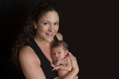 Mother with young baby. Happy mother with two week old baby girl, black background Stock Photo
