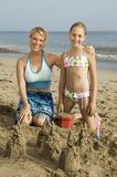 Mother and Young Daughter Building Sand Castle on Beach Royalty Free Stock Photography