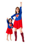 Mother and young daughter happily interacting together, both dressed in superman outfits with red skirts, all white royalty free stock photos