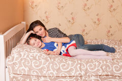 Mother and young daughter lies in bed. Royalty Free Stock Photo
