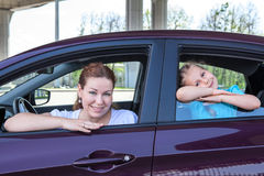 Mother and young daughter looking out from car windows Stock Photography