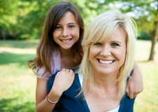 Mother and young daughter outside. Mother with young daughter on her back smiling Stock Image