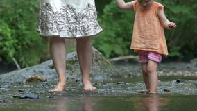 Mother and a young daughter paddle barefoot over rocks stock footage