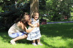 Mother with young daughter playing in park. Royalty Free Stock Photos