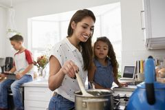 Mother and young daughter preparing food at hob in kitchen, pre-teen son sitting in the background royalty free stock photography