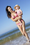 Mother With Young Daughter Running Along Beach Together Stock Photos