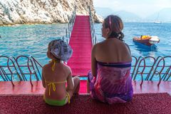 Mother and young daughter are traveling in the Mediterranean sea on the ship Stock Photos