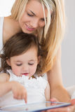 Mother and young daughter using digital tablet Royalty Free Stock Image