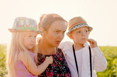 Mother with a young girl and boy. Mother with young girl and boy fashionable trendy sunhats posing together rural field  bright sun flare as they stare into Stock Images