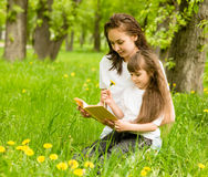 Mother with young girl reading book in park Stock Images