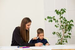 Mother and young son draws a picture at the table. Mother and young son draws a picture stock image